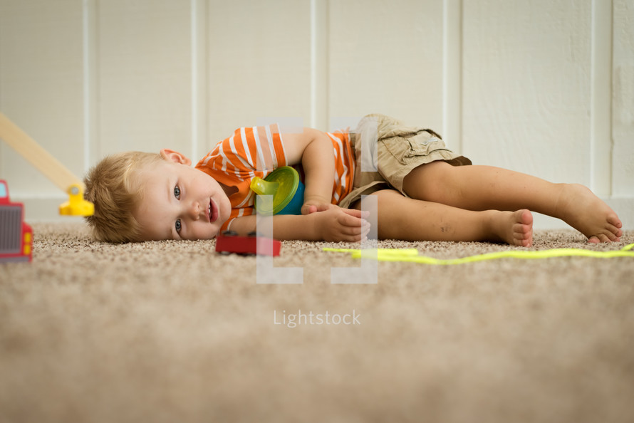 a toddler boy resting on the floor