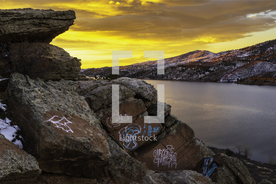 The sky bursts with color on Horsetooth Reservoir with graffiti on the boulders overlooking the lake