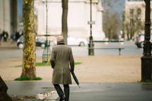 a businessman carrying an umbrella on a city sidewalk