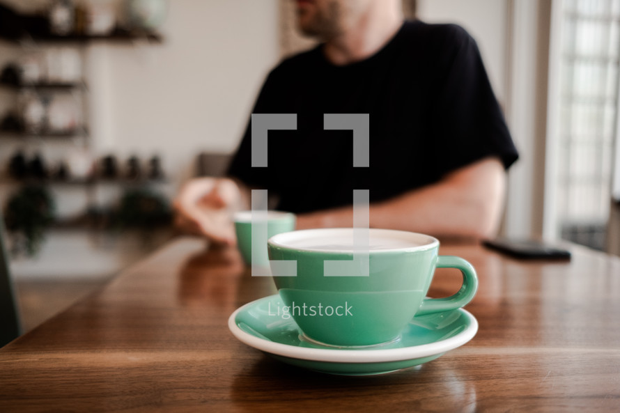 mint green coffee cup on a wood table