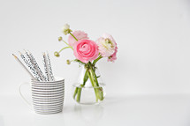 pink flowers in a vase and a mug of pencils