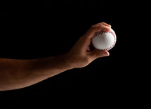 Baseball pitcher, close up of the hand ready to pitch on black background.