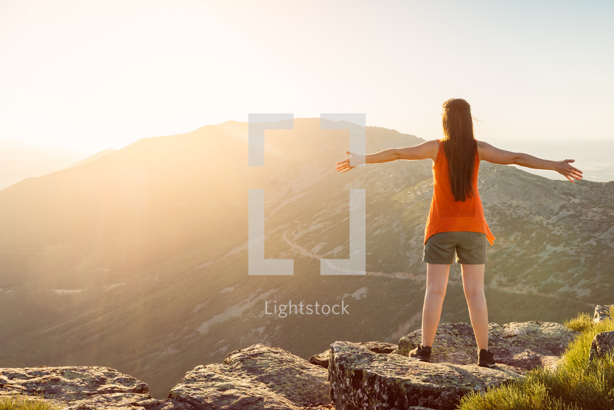 Happy woman with open arms stay on the peak of the mountain cliff edge under sunset light.