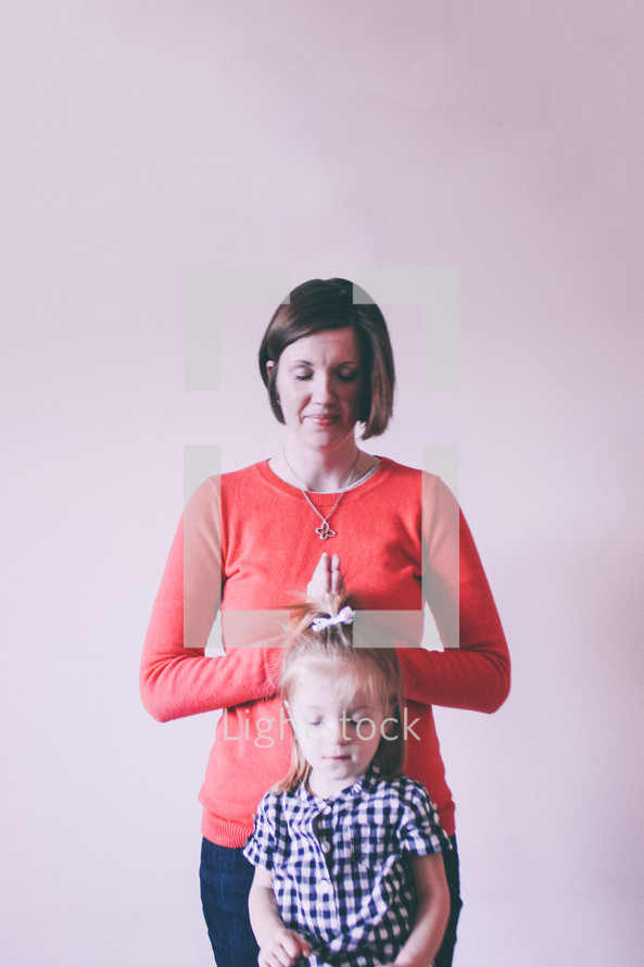 A woman praying over a child