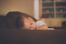 a toddler boy napping on a couch