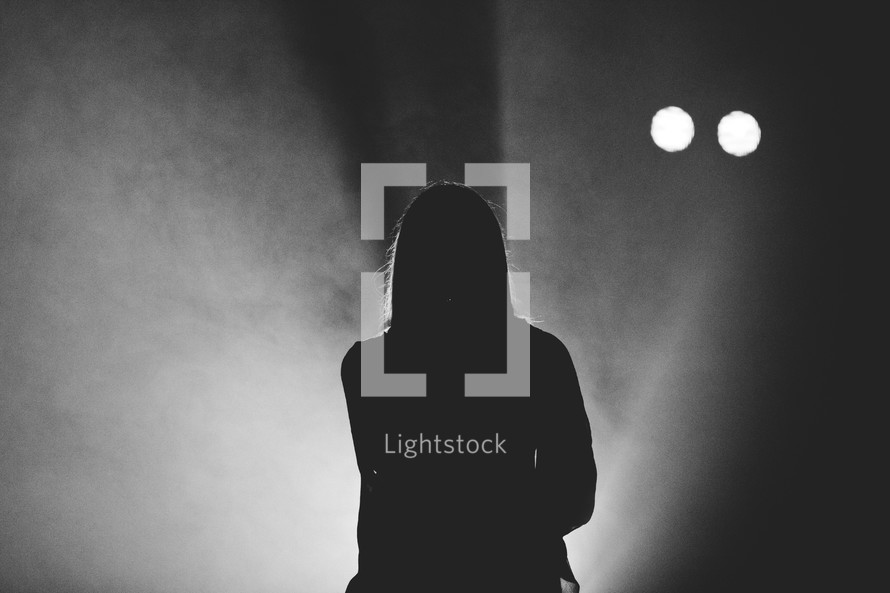 silhouette of a woman standing in a spotlight