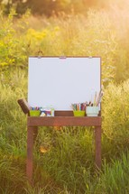 easel and paint and blank canvas outdoors