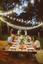 Guests at an outdoor evening dinner party.
