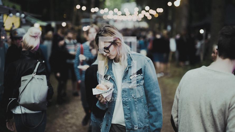 a woman walking through a crowd at a festival carrying a hamburger