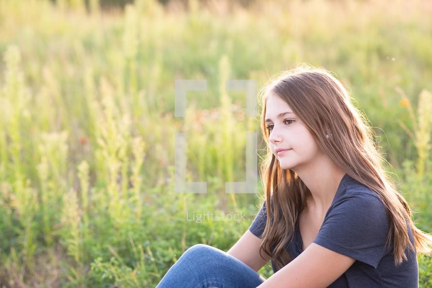 teen girl sitting outdoors thinking