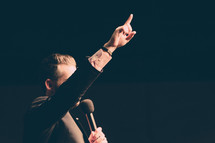 a preacher holding a microphone with a raised hands