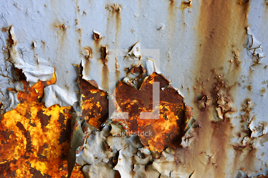 Grey paint peels to show rusted metal