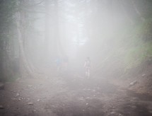 Man hiking through the misty woods.