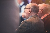 elderly men sitting in church pews at a worship service
