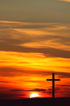 Sunrise behind a cross in silhouette
