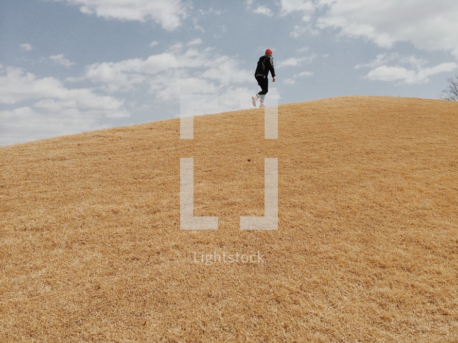 man running up a steep hill