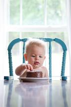 toddler boy eating birthday cake