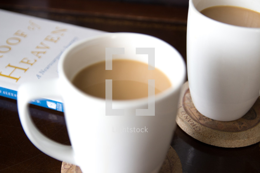 coffee mugs and book Proof of Heaven