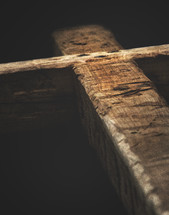 Light shining on a heavy wooden cross.