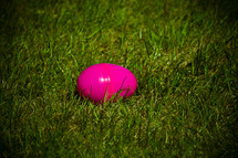 pink plastic Easter egg lying in the grass