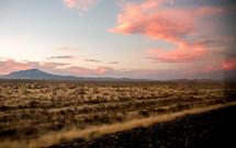 pink clouds over desert landscape