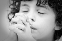A praying child with hands clasped.
