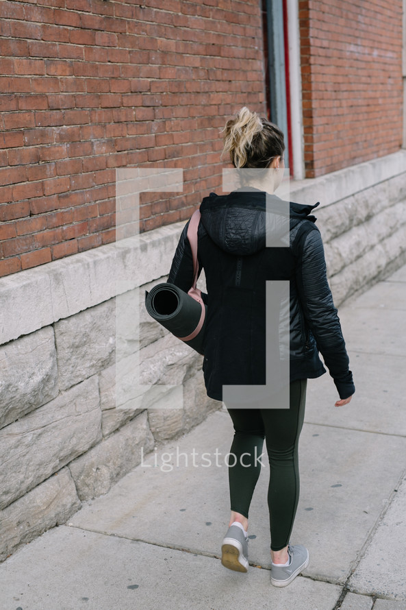 woman walking carrying a yoga mat