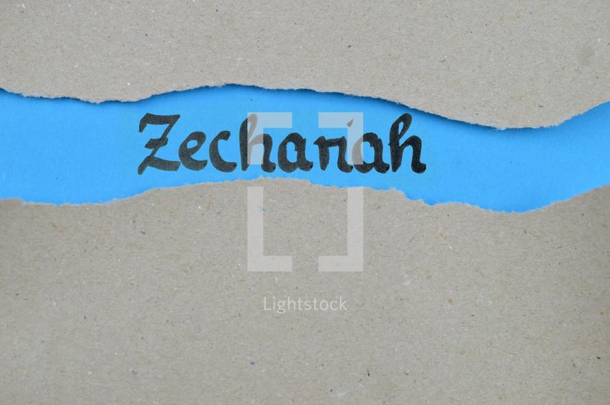 Zechariah - torn open kraft paper over blue paper with the name of the prophetic book Zechariah