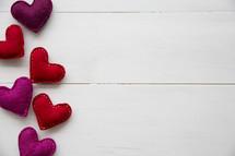 felt hearts on white wood background.