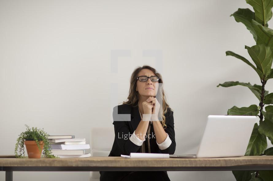 a businesswoman sitting behind a desk praying