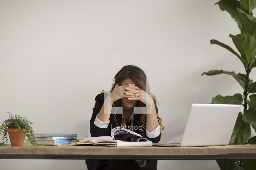 a woman working on a laptop computer with a headache