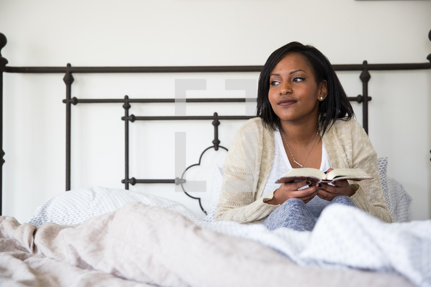 a young woman sitting in bed reading a book