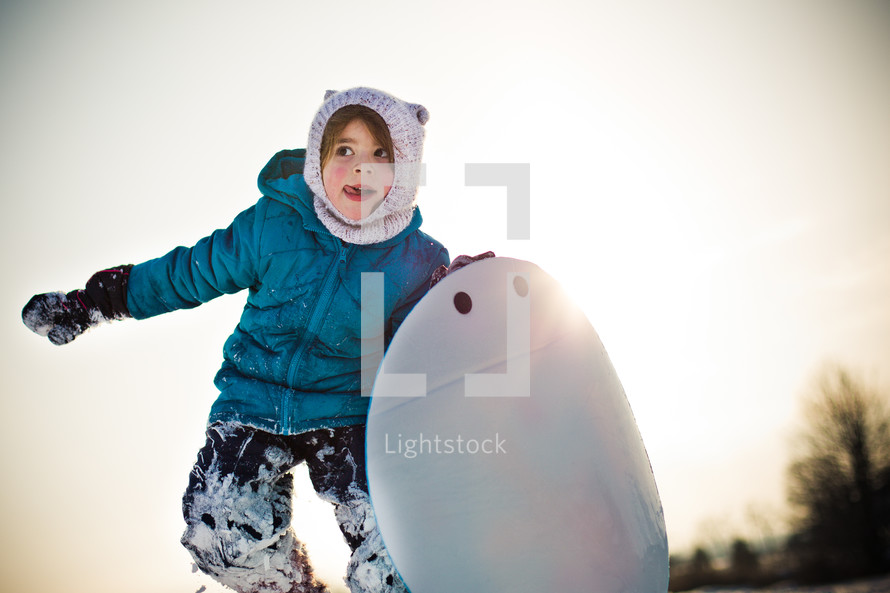 child in a winter hat and coat holding a circular sled