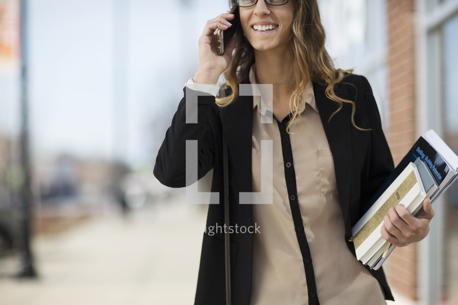 a woman walking carrying books and talking on a cellphone