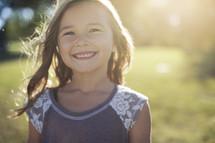 a smiling little girl outside.