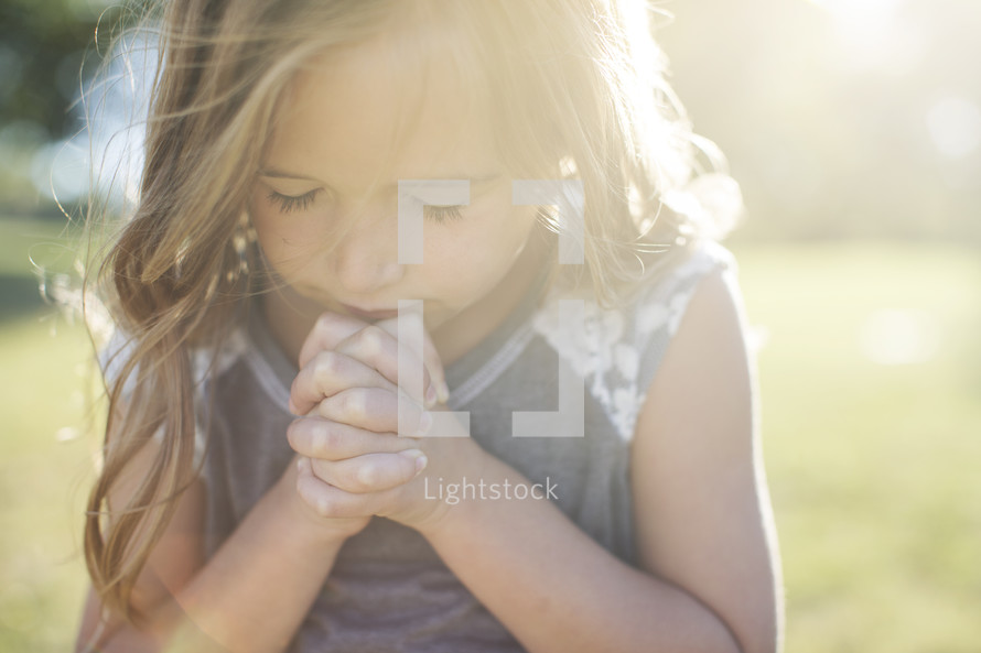 a girl child with praying hands