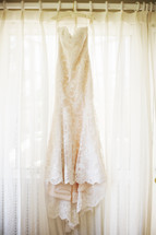 Wedding dress hanging in sunlit window.