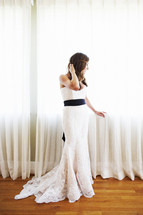 bride standing in front of a window draped with white curtains