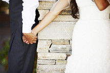 playful bride and groom holding hands
