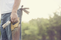 man holding a saw and paint brushes
