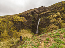 couple watching a waterfall on a green mountainside