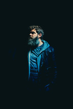 man with a thick beard standing in darkness