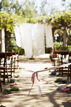 pink ribbon at the front of an aisle at an outdoor wedding ceremony
