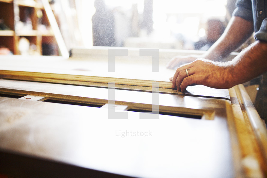carpentry - man cutting boards at a table saw
