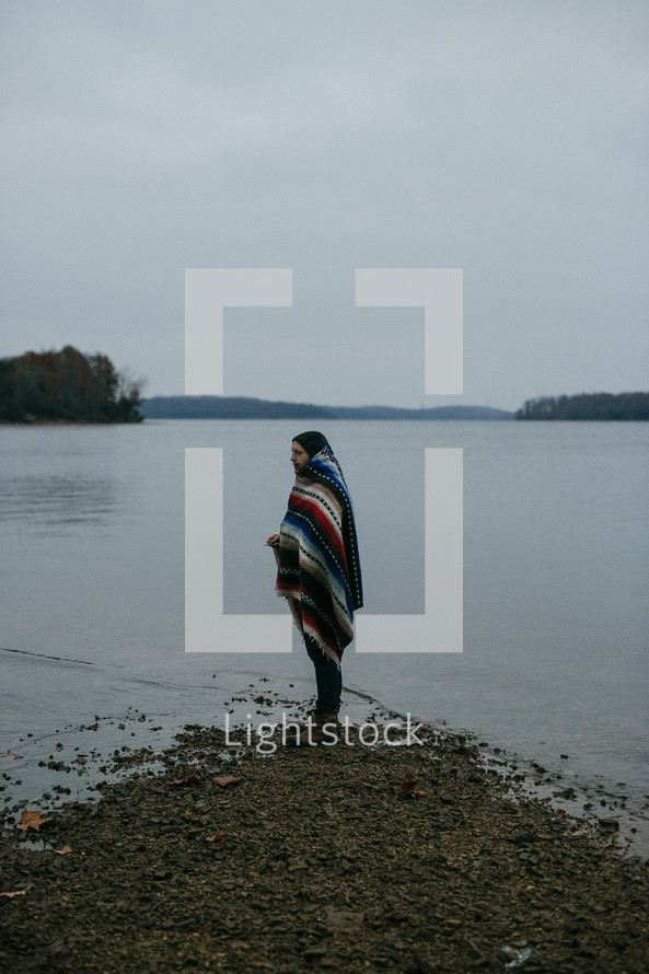 a man wrapped in a blanket standing on a lake shore