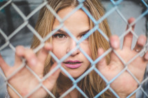 a woman behind a chain link fence