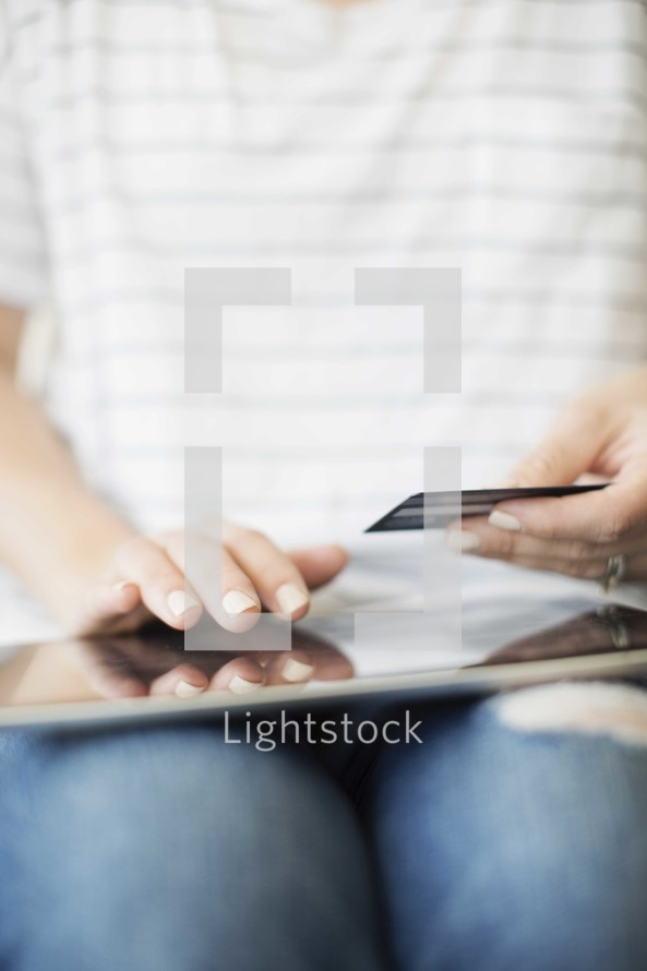 a woman holding a credit card and shopping online.