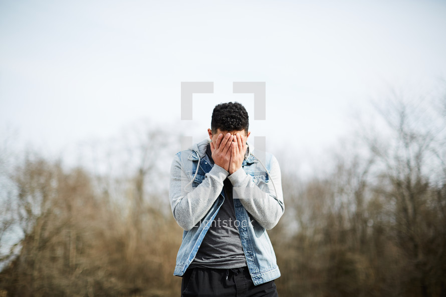 a young man covering his face with his hands