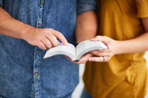 a man and woman standing reading the Bible together