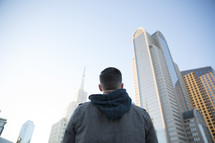 a man standing in a city looking up at the tall buildings.